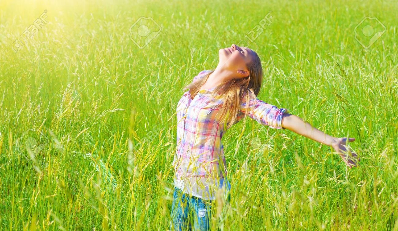 18522017-Woman-having-fun-outdoor-enjoying-fresh-air-and-spring-green-grass-freedom-and-happiness-concept-Stock-Photo
